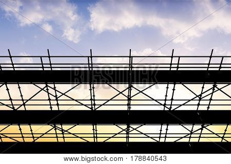 3d image of construction scaffolding against sunset with clouds