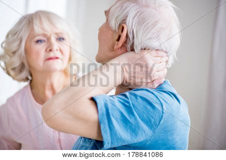 Back View Of Man With Neck Pain And Concerned Woman At Home