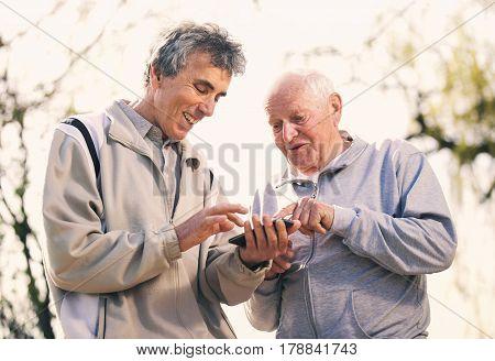 Two senior men using smart phone in the park
