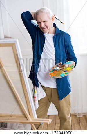 Portrait Of Focused Senior Man Drawing Picture In Art Workshop