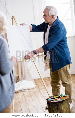 Senior Man Getting Ready To Draw Woman Portrait  In Workshop