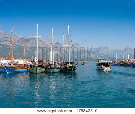 KEMER TURKEY - SEPTEMBER 8 2007: Touristic sailing boats stay in bay against mountains in Kemer Turkey on September 8 2007.