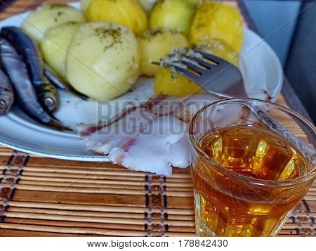 Cooked potatoes, spicy sprat, lard, vodka - dinner from natural products. Close-up