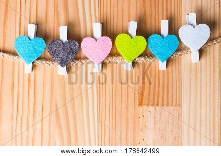 Colorful hearts on twine on natural wooden background. Copy space on the bottom.