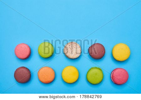 Top view of sweet macaroons with copy space over blue flatlay. Two lines of colourful macaroons