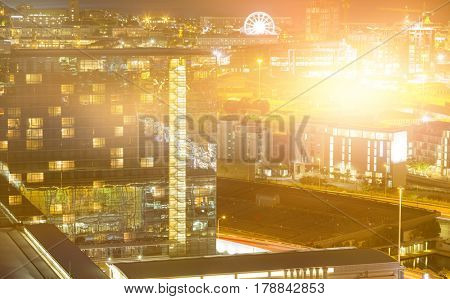 Blurry animated flare against illuminated beautiful buildings in city