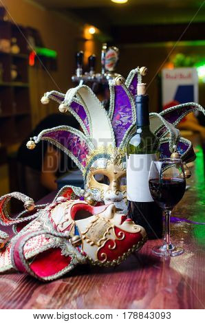 Close up beautiful Masquerade mask and red wine.