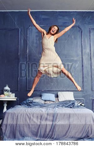 Low angle of an attractive young woman jumping energetically on the bed. Extremely excited woman in nightgown jumping on bed with arms and legs outstretched