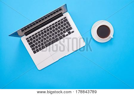 Top view of a silver stylish notebook computer with a cup of coffee close by. Small cup with aroma coffee placed on a flatlay