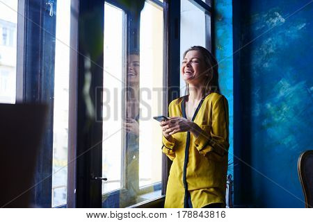 Laughing young girl with telephone in hands standing next to the window. Girl in yellow blouse. Darkblue walls, obscure atmosphere