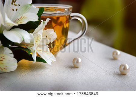 still life with green tea, white flowers and pearls. Still life with tea in a transparent Cup. Green tea in glass Cup, flowers and pearls.