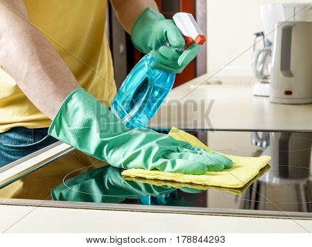 Man Cleaning The Cooker In The Kitchen