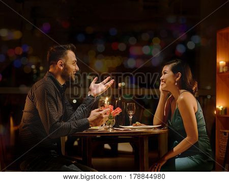 Young Caucasian man telling funny stories to his Vietnamese girlfriend during romantic date