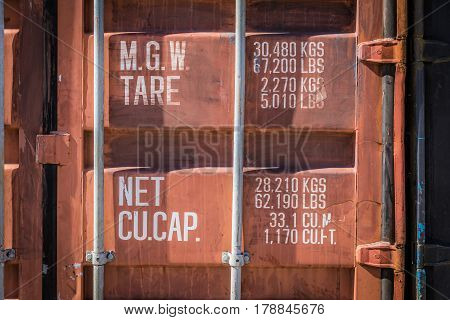 Old red container with weights and dimensions indications