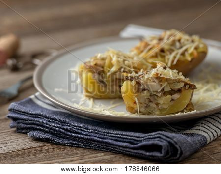 Served potion of baked potato stuffed with mushrooms and plenty of cheese, blue towel