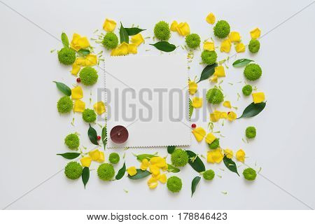 Candle and sheet of paper with pattern from petals of chrysanthemum flowers, ficus leaves and ripe rowan on white background. Overhead view. Flat lay.