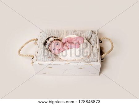 Infant with her eyes open widely looking from the basket, pastel colored wrapping