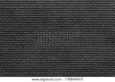 the abstract textured background of black color of polymeric material or synthetic fabric with a corrugated symmetric pattern and with small droplets of water