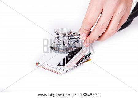 Hands holding stethoscope on credit cards as symbol of money care and growth or investment. Isolated.