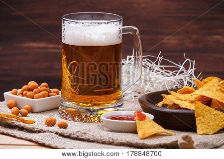 Glass of beer. Nachos chips. Tortilla snack. Mexican salsa nuts. Appetizer with sweet salsa or chilli sauce. Mug or pint of ale. On rustic wooden background.