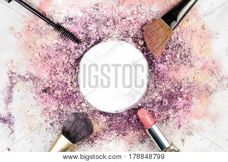Makeup brushes, lipstick, and mascara applicator on white marble background, with traces of powder and blush forming frame with copy space