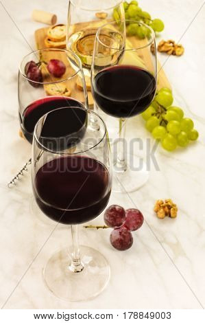 Glasses of red and white wine at a tasting, with grapes and a place for text