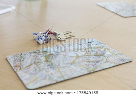 close up on place mat with a touristic mal of Amsterdam city center and a set of keys on a Dutch wooden shoes key ring