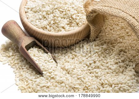 white rice in wooden bowl and juta bag closeup on white background