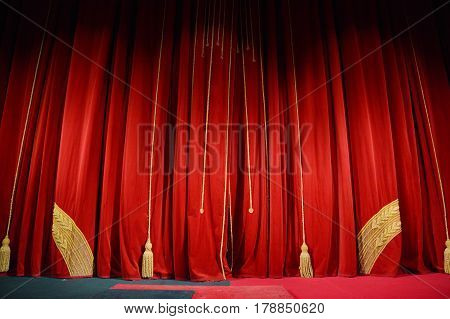 red theater curtain on a theater stage with gold embroidery