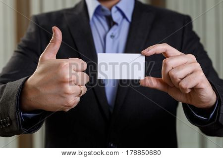 Businessman holding visit card. Man showing blank business card. Person in black suit showing thumb up. Mock up design.