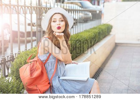 Cute playful young woman reading a book and sending a kiss in the city