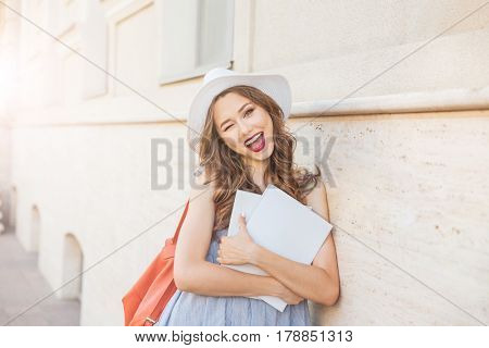 Cheerful pretty young woman in hat with blank covered magazines winking and showing thumbs up