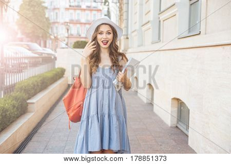 Happy surprised young woman in hat with backpack and magazines standing on the street