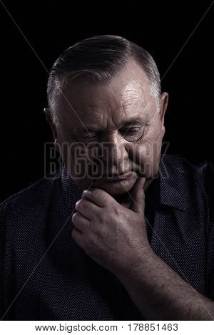 Close up portrait of pensive aged man wearing shirt, looking down, holding hand under his chin against black background - retirement concept