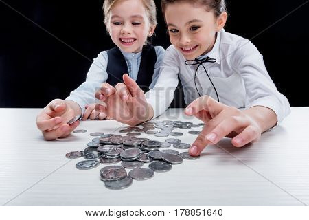 Portrait Of Little Girls Sitting At Table And Calculating Money On Black