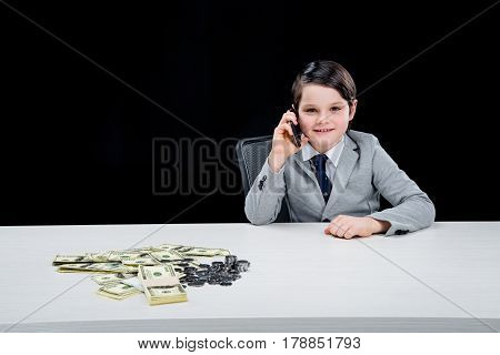 Portrait Of Smiling Boy Playing Businessman And Talking On Smartphone On Black