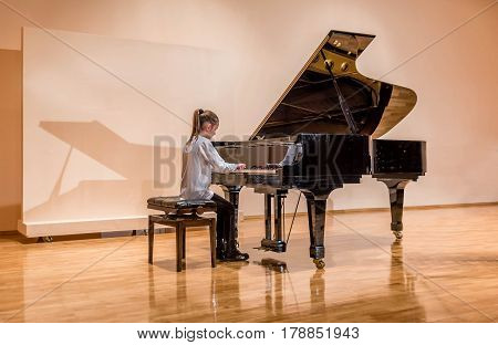 Little girl playing the piano at the concert