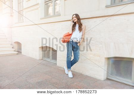 Young happy beautiful brunette woman talking on the phone while leaning on the wall outdoors