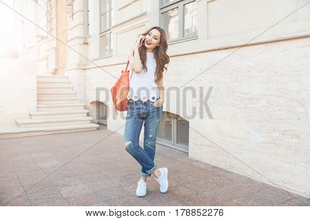 Full length portrait of a happy cheerful girl talking on the phone