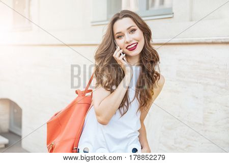 Happy cheerful young girl talking on the phone standing outdoors