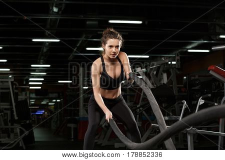 Picture of concentrated young strong sports lady make sport exercises in gym with ecquipment and looking aside.
