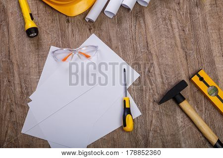 Screwdriver, hammer and helmet. Flashlight, building level and protective glasses. Blank sheet of paper. Architecture plans.