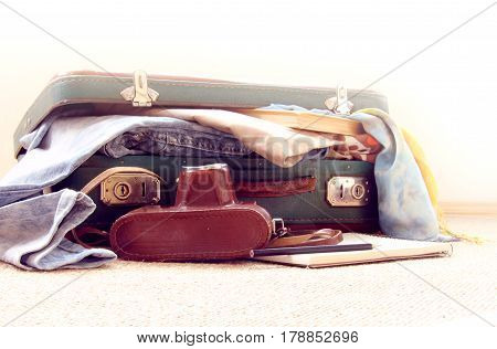 old camera and half-open suitcase with clothes / fees in retro journey