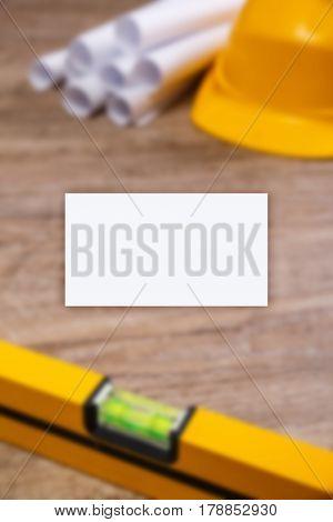 Business card mockup. Helmet, paper plans and building level. Construction design. Wood rustic background.