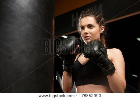 Image of concentrated young strong sports lady boxer make boxing exercises in gym and looking aside.