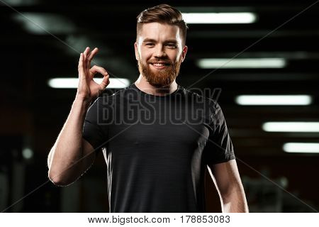 Image of cheerful sports man standing and posing in gym and looking at camera while showing okay gesture.