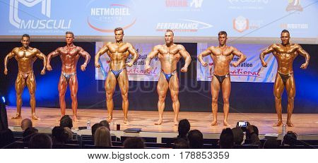 MAASTRICHT THE NETHERLANDS - OCTOBER 25 2015: Male bodybuilders Ali Rezah from Iran with other competitors flex their muscles and show their best physique in a front pose on stage at the World Grandprix Bodybuilding and Fitness of the WBBF-WFF