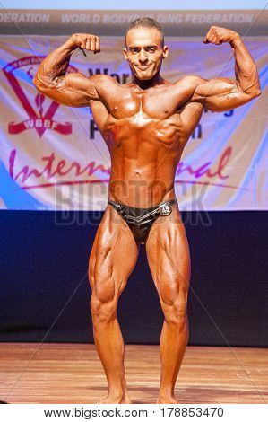 MAASTRICHT THE NETHERLANDS - OCTOBER 25 2015: Male bodybuilder flexes his muscles and shows his best front double biceps double biceps pose at the World Grandprix Bodybuilding and Fitness of the WBBF-WFF