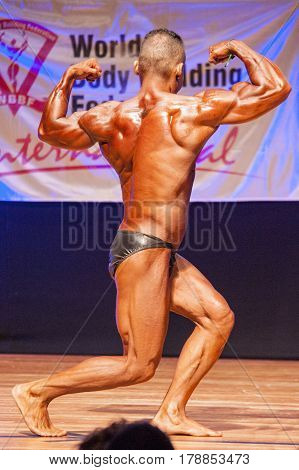 MAASTRICHT THE NETHERLANDS - OCTOBER 25 2015: Male bodybuilder flexes his muscles and shows his best back double biceps pose at the World Grandprix Bodybuilding and Fitness of the WBBF-WFF