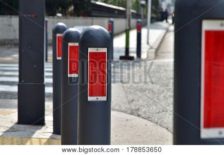 Scenery of pole and reflector plate beside sidewalk